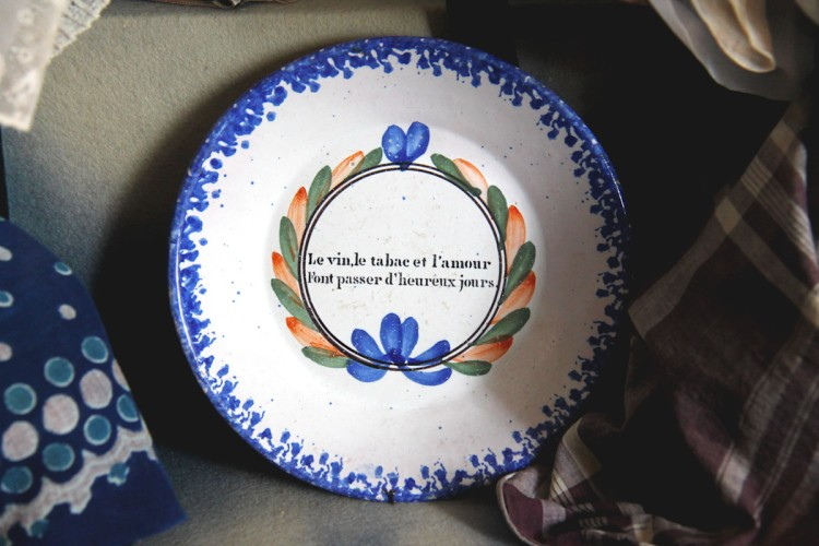 """Assiette portant l'inscription """"le vin, le tabac et l'amour font passer d'heureux jours"""" , à la salle des coiffes, au Musée Dupuy-Mestreau de Saintes"""
